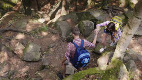 A-Man-Helps-A-Woman-To-Climb-A-Steep-Path-Trekking-In-The-Forest-Hiking-And-Active-Lifestyle