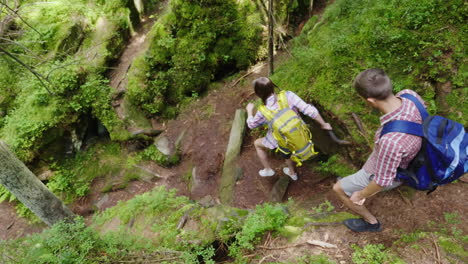 Friends-Go-Down-A-Steep-Montaña-Path-Traveling-And-Adventures-In-The-Forest-Active-Way-Of-Life