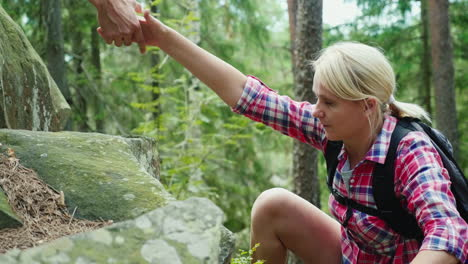 A-Woman-Climbs-A-Steep-Rock-She-Is-Given-A-Helping-Hand