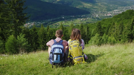 Young-Couple-Of-Tourists-With-Backpacks-Sitting-On-A-Green-Meadow-Looking-At-A-Picturesque-Mountain-