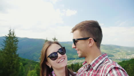 Young-Active-Couple-Taking-Pictures-Against-The-Backdrop-Of-A-Beautiful-Mountain-Landscape