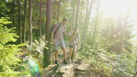 A-Young-Couple-Travels-Along-A-Picturesque-Place-In-The-Forest-A-Man-Helps-A-Woman-To-Walk-Along-The