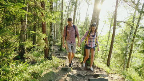 A-Couple-Of-Tourists-With-Backpacks-Go-On-A-Picturesque-Mountain-Path-In-The-Rays-Of-The-Setting-Sun