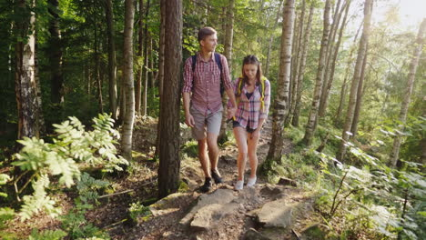 A-Young-Couple-Of-Tourists-Walking-Along-A-Mountain-Path-In-The-Rays-Of-The-Setting-Sun