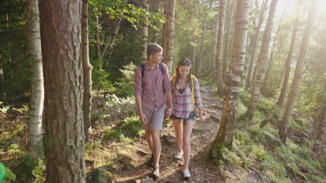 Young-Tourists-With-Backpacks-Walk-Along-A-Trail-In-The-Forest