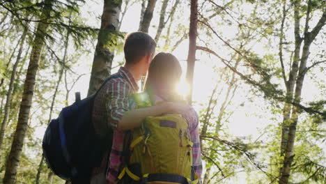 A-Young-Couple-Of-Tourists-Enjoy-A-Walk-In-The-Woods-At-Sunset-They-Stand-Hug-And-Look-Forward-Back-