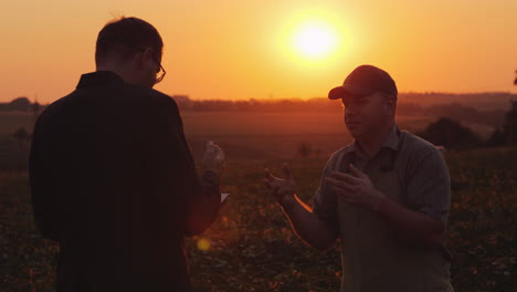 Farmer-Discussing-With-A-Businessman-In-A-Field