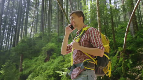 A-Person-Uses-A-Smartphone-In-A-Hike-Sits-By-A-Beautiful-Forest