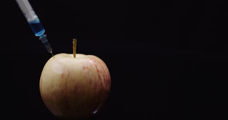 Food-Genetic-Modification-Syringle-Injecting-Liqquid-In-Apple-Gmo-Modification-Concept-1