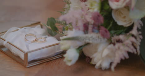 Wedding-Rings-In-Decorated-Box-With-Flowe-Background-