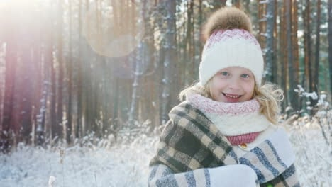 Portrait-Of-A-Happy-Little-Girl-Wrapped-In-A-Plaid-In-A-Snow-Covered-Winter-Forest