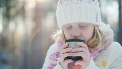 A-6-Year-Old-Girl-Drinks-Hot-Tea-On-The-Street-Against-The-Background-Of-The-Winter-Forest-Slow-Moti