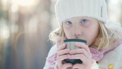 A-Little-Girl-In-A-Warm-Knitted-Hat-Drinks-Hot-Tea-From-A-Thermos-In-The-Winter-Forest-Portrait-In-T