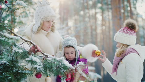 Mom-With-Two-Little-Girls-Preparing-For-Christmas-Decorate-The-New-Year-Tree-With-Round-Balls-In-A-S