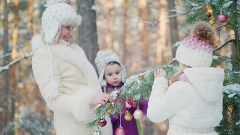 Two-Sisters-And-Mother-Decorate-The-Fir-In-The-Courtyard-Of-The-House-With-New-Year\-s-Toys-On-A-Wint
