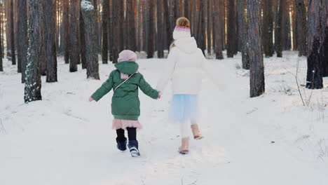 Two-Carefree-Little-Girls-Running-Through-The-Winter-Forest-Back-View