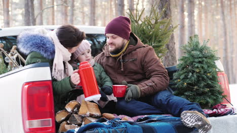 A-Young-Family-Of-Three-People-Is-Drinking-Hot-Tea-From-A-Thermos-Sitting-In-The-Back-Of-A-Car-Near-