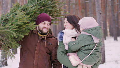 Two-Parents-With-A-Child-Driving-A-New-Year-Tree-On-A-Sled-On-A-Snowy-Forest-4K-Video