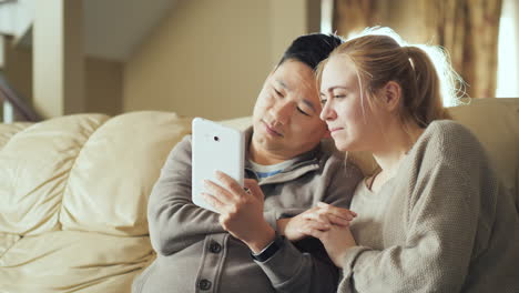 Young-Couple-Enjoys-Tablet-In-House