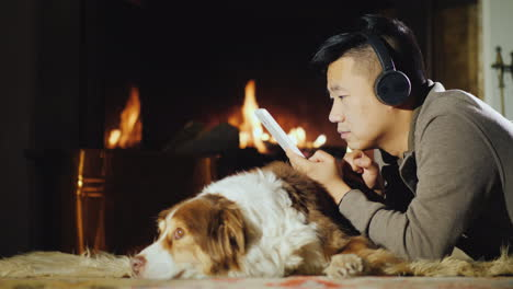 Asian-Man-Uses-A-Tablet-Lies-Near-The-Fireplace-01