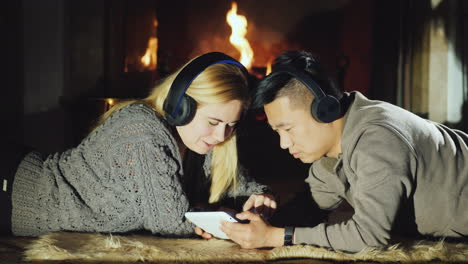 Young-Couple-Sharing-Tablet-By-Fireplace-02