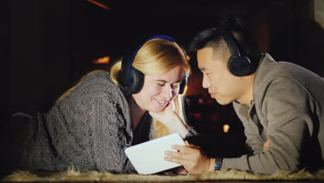 Young-Couple-Enjoys-Tablet-Lie-Near-Fireplace
