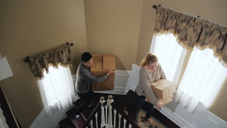 Young-Multi-Ethnic-Couple-Carries-Boxes-Of-Things-Up-The-Stairs