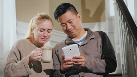 Young-Couple-Enjoys-Tablet-In-House-Sitting-On-Stairs