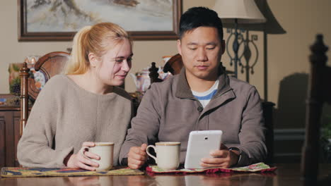 Young-Couple-Drink-Coffee-Together-Watch-The-News-On-A-Tablet