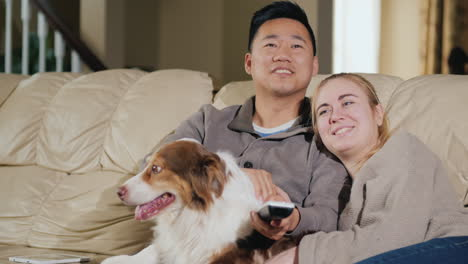 Young-Loving-Couple-With-Dog-Sit-On-The-Couch-Watching-Tv