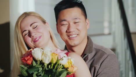 Portrait-Of-A-Young-Multi-Ethnic-Couple-A-Woman-Holding-Flowers
