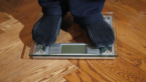 Man-Weighs-Himself-On-Floor-Scales-01