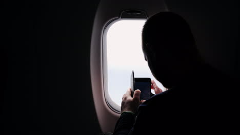 A-Silhouette-Of-A-Man-Taking-Pictures-Of-The-View-From-The-Plane-Window