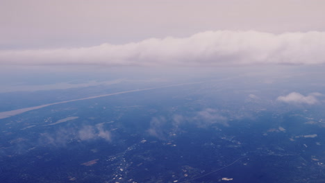 View-From-The-Plane-Window-To-The-Ground-Far-Below-And-Clouds