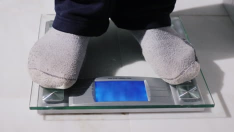 Man-Weighs-Up-On-Floor-Scales