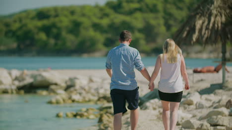Couple-Walking-On-Sea-Shore