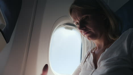 A-Young-Woman-Is-Reading-A-Magazine-In-The-Cockpit-Of-An-Airplane-Comfort-And-Entertainment-In-The-J