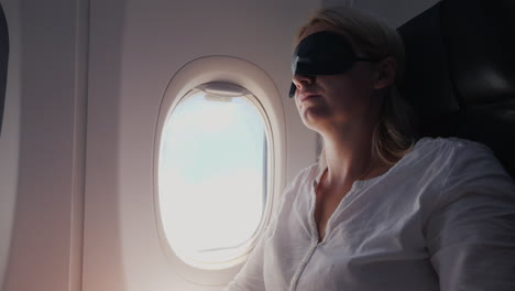 A-Young-Woman-With-A-Dark-Bandage-In-Her-Eyes-Sleeps-In-The-Cabin-Of-A-Passenger-Aircraft-Traveling-