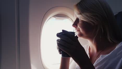 A-Woman-Is-Drinking-Coffee-In-The-Cabin-Of-An-Airplane-Sits-By-The-Window