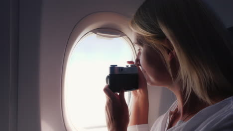A-Woman-Photographs-A-Beautiful-View-From-The-Window-Of-An-Airplane