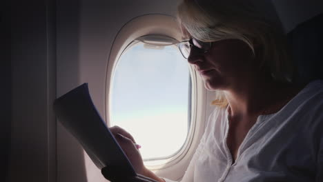 Business-Woman-Is-Reading-Documents-On-The-Plane-Business-And-Travel
