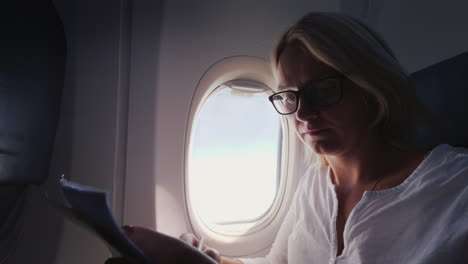 Young-Business-Woman-Looks-Through-Documents-In-Flight-Business-And-Travel