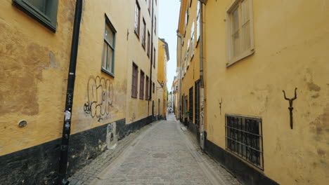 Walk-Along-A-Narrow-Street-Between-The-Walls-Of-Houses-In-Stockholm-Steadicam-Shot