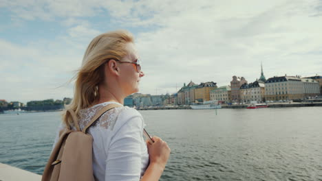 A-Woman-With-A-Pink-Backpack-Admires-A-Beautiful-View-Of-The-City-Of-Stockholm-In-Sweden-Journey-Thr
