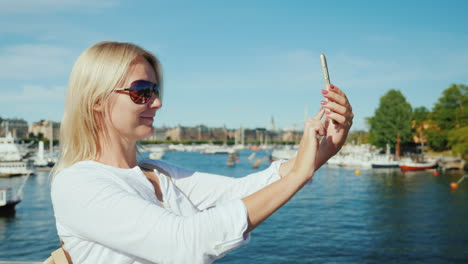 A-Woman-Uses-A-Smartphone-On-A-Bridge-Overlooking-Stockholm-Sweden