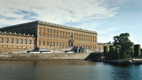 The-Royal-Palace-In-Stockholm-A-Clear-Summer-Day-A-Number-Of-Tourist-Buses-Are-Parked-Nearby