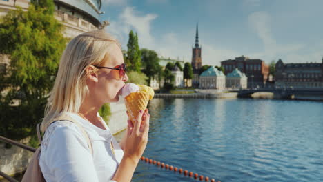 Woman-Tourist-Eating-Ice-Cream-On-The-Background-Of-The-Recognizable-View-Of-The-City-Of-Stockholm-I
