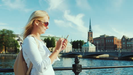 A-Young-Woman-Uses-A-Smartphone-Against-The-Background-Of-The-City-Line-Of-Stockholm-Sweden-Always-I
