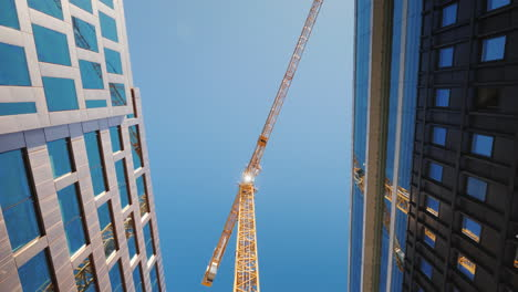A-Huge-Construction-Crane-Near-Office-Buildings-With-Glass-Facades-City-Building-Steadicam-Shot