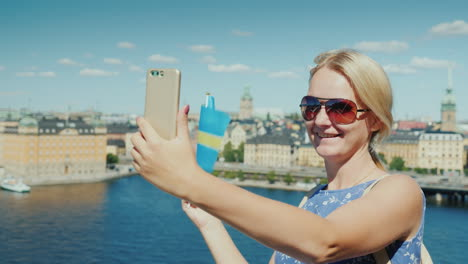 A-Happy-Tourist-With-The-Flag-Of-Sweden-Takes-Pictures-Of-Himself-Against-The-Backdrop-Of-Stockholm-